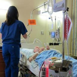 un anziano allettato in ospedale, mentre viene assistito dal personale sanitario